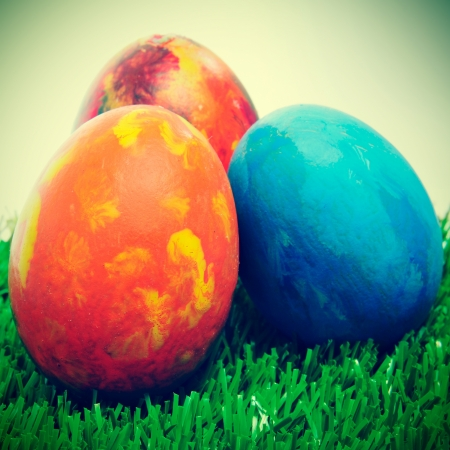 christian festival: some easter eggs of different colors on the grass, with a retro effect
