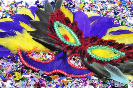 some carnival masks with feathers of different colors on a pile of confetti Stock Photo - 17553022