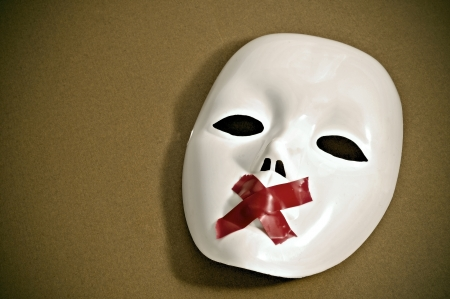 dictatorship: white mask with red tape strips forming a cross in its mouth on a brown background