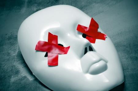 dictatorial: Maschera bianca con strisce di nastro rosse che formano croci nei suoi occhi su sfondo blu