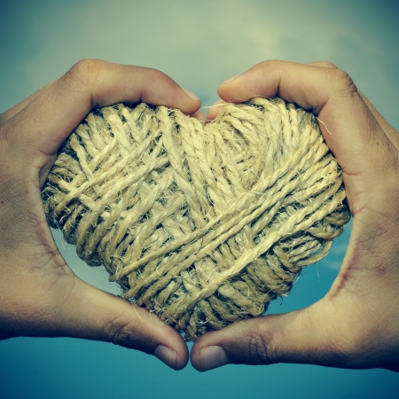 man hands forming a heart showing a heart-shaped coil of rope photo