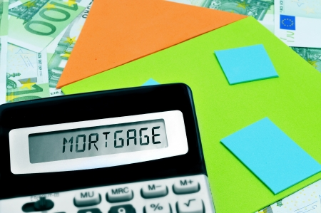 mortgage rates: word mortgage written in the display of a calculator, and a depiction of a house on a pile of euro bills