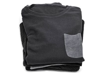 pullovers: a pile of folded pullovers on a white background