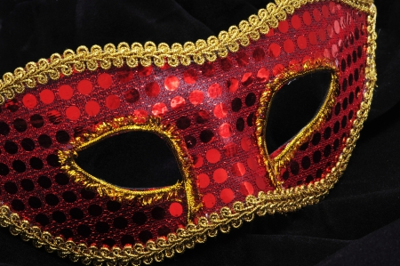 fancy dress party: an elegant red and golden carnival mask on a black fabric background