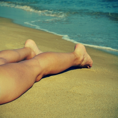 a man laying on the shore of a beach in the summer Stock Photo - 17795126