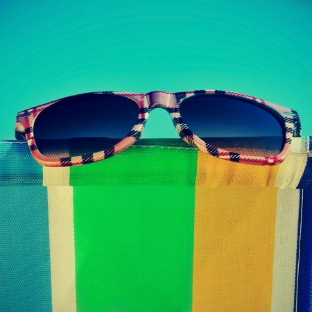 a pair of sunglasses on a colorful deckchair on the beach photo