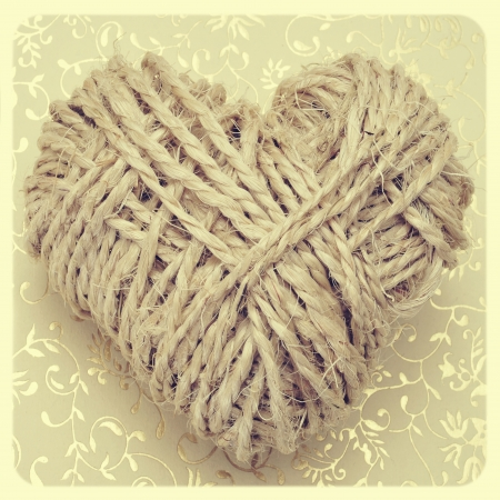 heart-shaped coil of rope on a textured background, with a retro effect photo