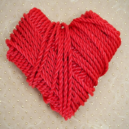 lunares rojos: en forma de corazón rollo de cuerda roja sobre un fondo de textura