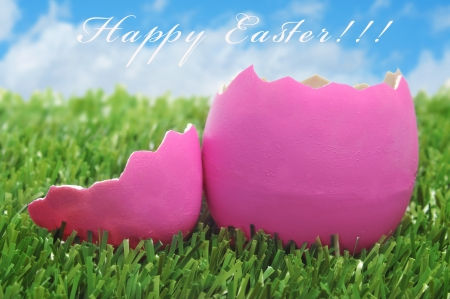 an open pink easter egg on the grass and the sentence happy easter photo