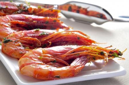 tapas españolas: primer plano de un plato con camarones cocidos españoles con ajo y perejil Foto de archivo