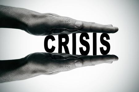 crisis economica: las manos del hombre presionando la palabra crisis, en blanco y negro
