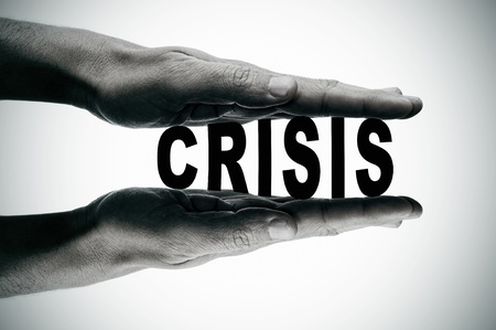 man hands pressing the word crisis, in black and white photo