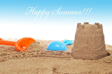 sandcastle and shovels on the sand of a beach and the sentence happy summer photo