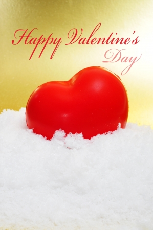 a red heart on the snow on a golden background and the sentence happy valentines day photo