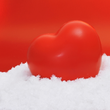 a red heart on the snow on a red background Stock Photo - 17795305