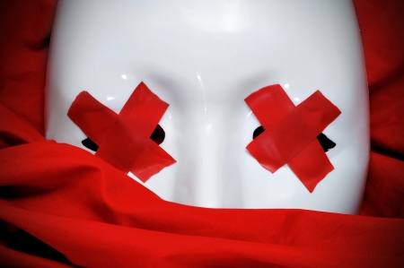 dictatorial: white mask with red tape strips forming crosses in its eyes on a red fabric background Stock Photo