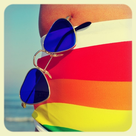 heartshaped: someone wearing a rainbow swimsuit and heart-shaped sunglasses on the beach, with a retro effect