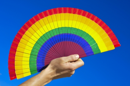 someone holding a hand fan painted with the colors of the gay pride flag over the blue sky photo