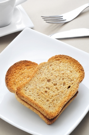 a plate with two bread rusks forming a heart on a table with a cup of coffee photo