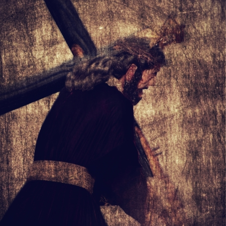 golgotha: Jesus Christ carrying the Holy Cross on a vintage background