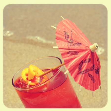 closeup of a cocktail on the sand of a beach, with a retro effect Stock Photo - 17948979