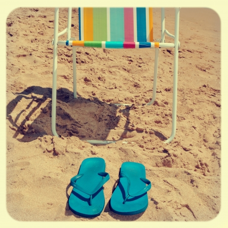flipflops: a deckchair and a pair of flip-flops on the beach, with a retro effect