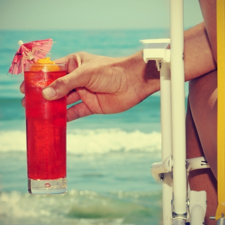 someone chilling out with a cocktail on the beach, with a retro effect Stock Photo - 17948982