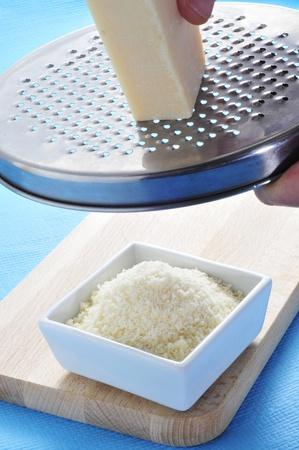 queso rallado: alguien rejilla un trozo de queso Parmigiano-Reggiano Foto de archivo