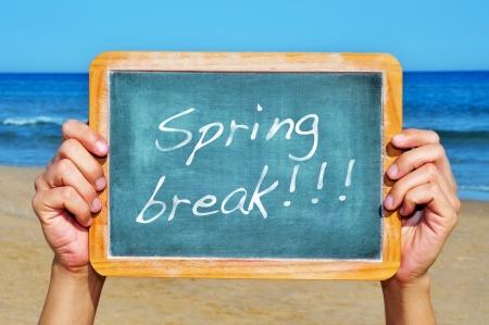 sentencia: alguien que sostiene una pizarra en blanco en la playa con las vacaciones de primavera frase escrita en el mismo Foto de archivo
