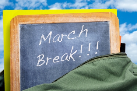 march break written in a blackboard in a school bag with books photo