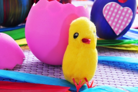 some easter eggs painted in different colors and patterns, one of them broken and a teddy chick photo