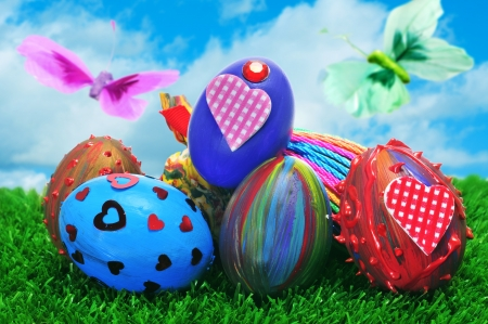 a pile of easter eggs painted in different colors and patterns on the grass with butterflies photo