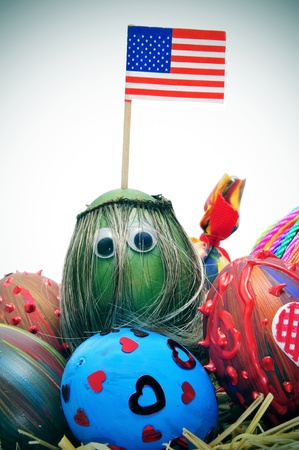a pile of easter eggs painted in different colors and patterns, one of them with long hair and eyes, and the american flag photo