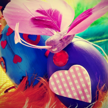 a pile of easter eggs painted in different colors and patterns, with feathers and butterflies photo