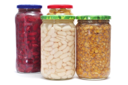garbanzo bean: some jars with different preserved legumes, such as white beans, red beans, lentils and chickpeas on a white background Stock Photo