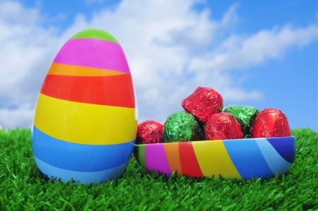 an easter egg of different colors, full of chocolates, on the grass photo