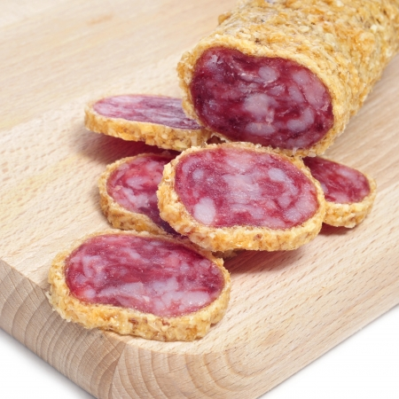 llonganissa: some slices of fuet, spanish sausage, coated with onion, in a wooden chopping board