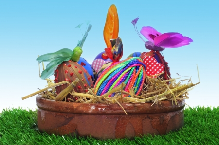 a pile of easter eggs painted in different colors and patterns in a earthenware bowl with straw, on the grass photo