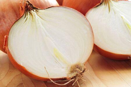 onions: algunas cebollas marrón cortado en mitades sobre una mesa de madera Foto de archivo