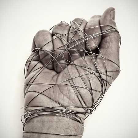 man hand tied with wire, as a symbol of oppression or repression, on a white background photo