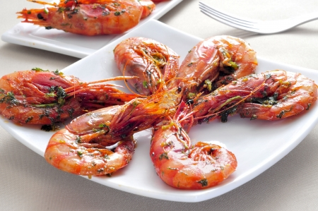ajillo: closeup of a plate with spanish shrimps cooked with garlic and parsley, served as tapas