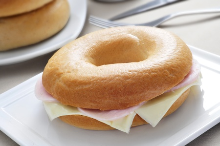 doughy: closeup of a plate with a bagel stuffed with cheese and ham on a table