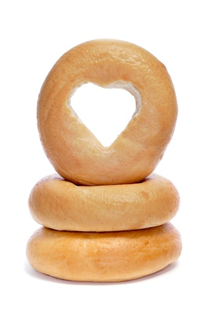 a pile of plain bagels with a heart-shaped hole on a white background photo