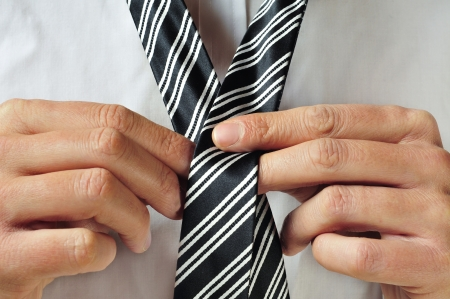 gray suit: a man knotting his tie
