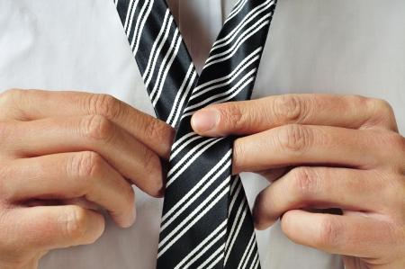 knotting: un uomo che annoda la cravatta