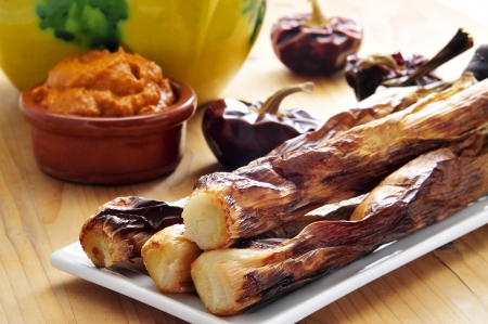 calsotada: closeup of a plate of barbecued calcots, catalan sweet onions, and a bowl with romesco sauce Stock Photo