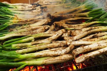calsotada: a pile of calcots, typical catalan sweet onions, on the barbecue