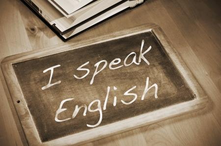 sentencia: frase que habla Ingl�s escrito con tiza en una pizarra, en una mesa con libros Foto de archivo