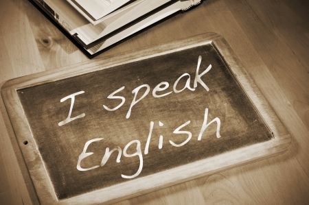 assertion: sentence I speak english written with chalk on a blackboard, on a table with books