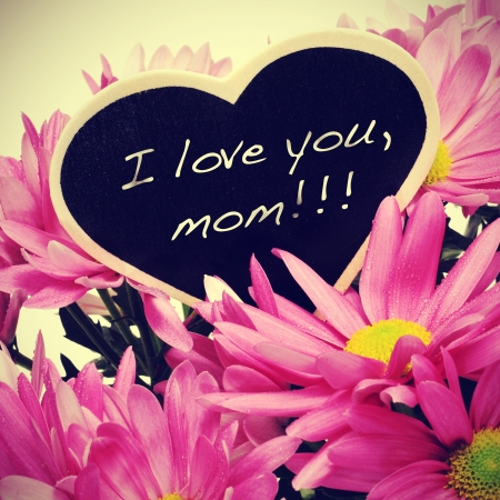 sentence I love you, mom written with chalk on a heart-shaped blackboard on a bouquet of pink chrysanthemums, with a retro effect photo